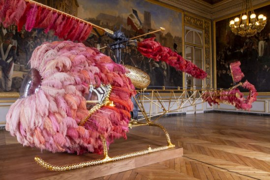 Lilicoptère, 2012. Bell 47 helicopter, ostrich feathers, Swarovski crystals, gold leaf, industrial coating, dyed leather upholstery embossed with fine gold, Arraiolos rugs, walnut wood, wood grain painting, passementerie. 300 x 274 x 1265 cm Courtesy Haunch of Venison/Christie's, London. Work produced in collaboration with Fundação Ricardo do Espírito Santo Silva, Lisbon. 2012 Joana Vasconcelos Versailles, Château de Versailles, Versailles, photo © Joana Vasconcelos.