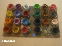 """""""Shot Glasses for Gouache Paint holders Mounted on Plywood"""", MAURO MALANG SANTOS (b.1928), Undated, Collection of the Artist. After mixing his peculiarly saturated colors, Malang found shot glasses as ideal containers in which to dip his brush before applying paint on his canvasses. He used a wooden base especially fabricated to hold the shot glasses in place."""